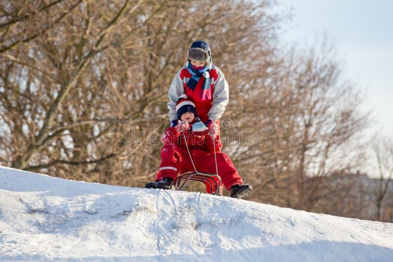 Twee jongens bij de slee op de bovenkant van sneeuwheuvel die op ridi wachten stock afbeelding