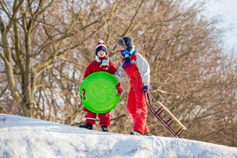 Twee jongens bij de slee op de bovenkant van sneeuwheuvel die op ridi wachten stock afbeeldingen