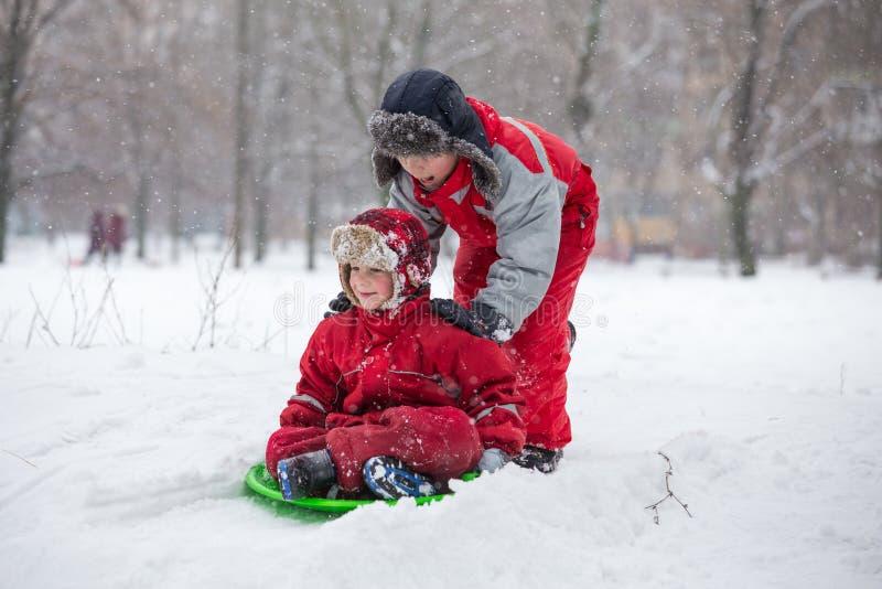 Twee jongens die bij de dia op sneeuwpark berijden stock fotografie
