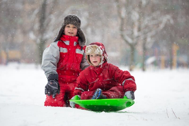 Twee jongens die bij de dia op sneeuwpark berijden stock foto's