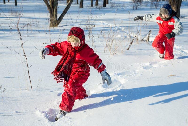 Twee jongens die bij de sneeuw op park lopen royalty-vrije stock foto's