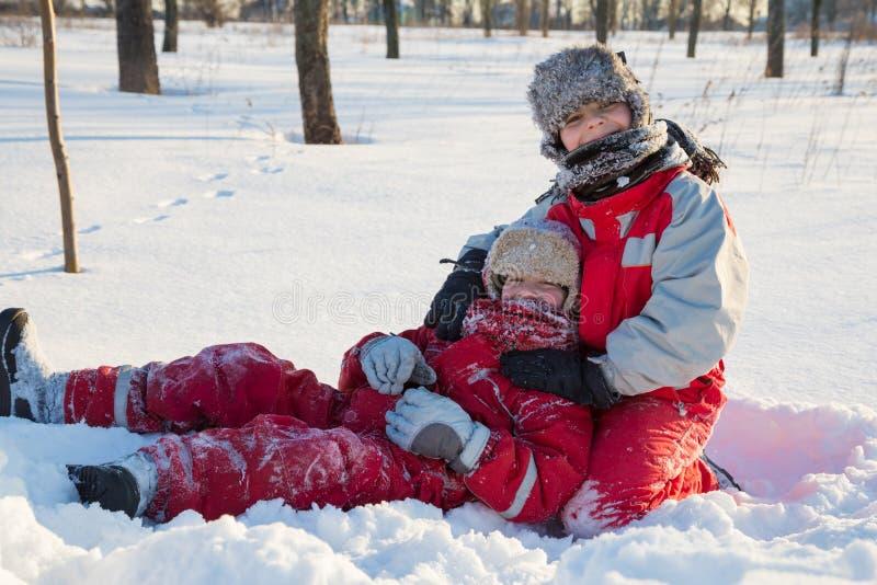 Twee jongens die bij de winter spelen parkeren royalty-vrije stock afbeelding