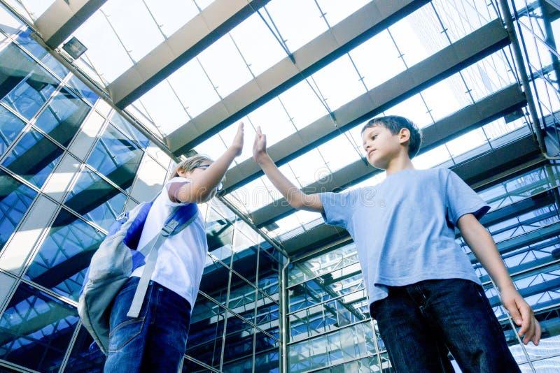 Twee jongens die elkaar een hoogte vijf in openlucht geven royalty-vrije stock foto