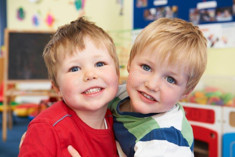 Twee Jongens die elkaar op Preschool koesteren stock foto