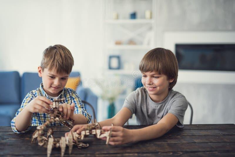 Twee jongens die en grote aannemer thuis samen glimlachen maken stock fotografie