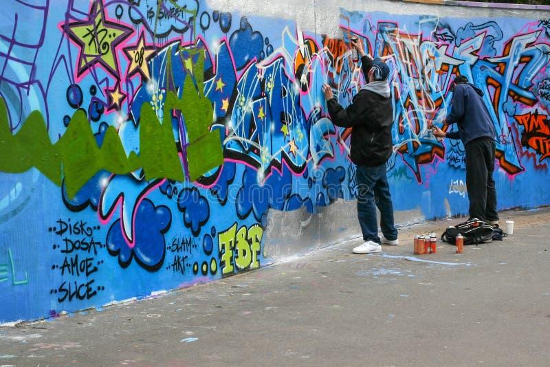 Twee jongens die graffiti bespuiten stock fotografie