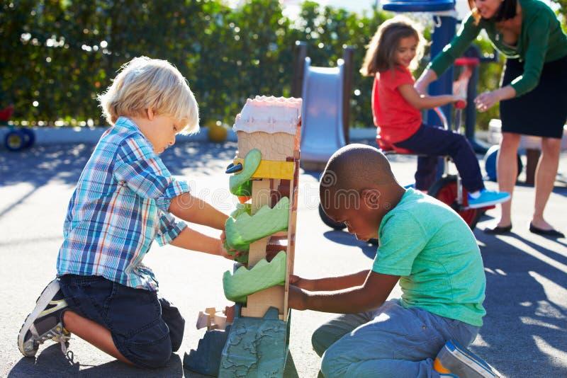 Twee Jongens die met Toy In Playground spelen stock fotografie
