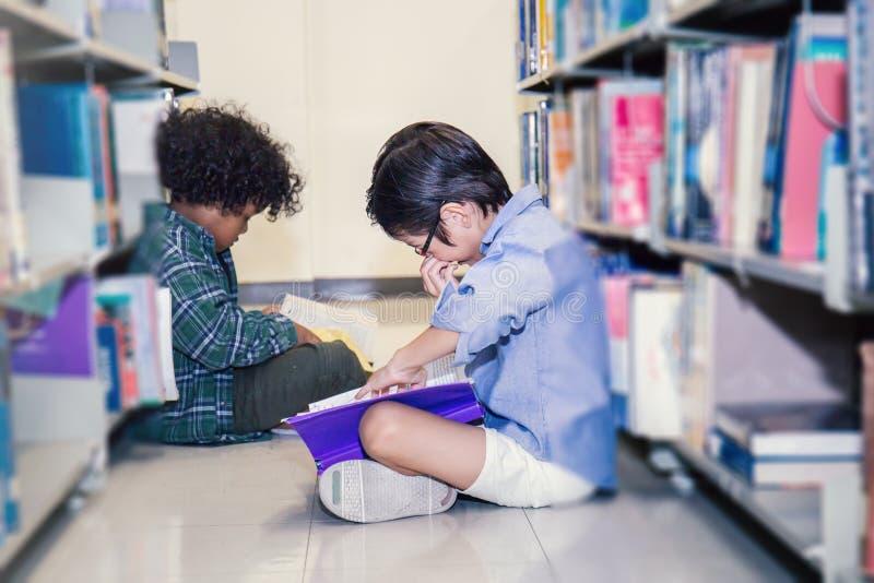 Twee jongens die op de bibliotheekvloer lezen stock afbeelding