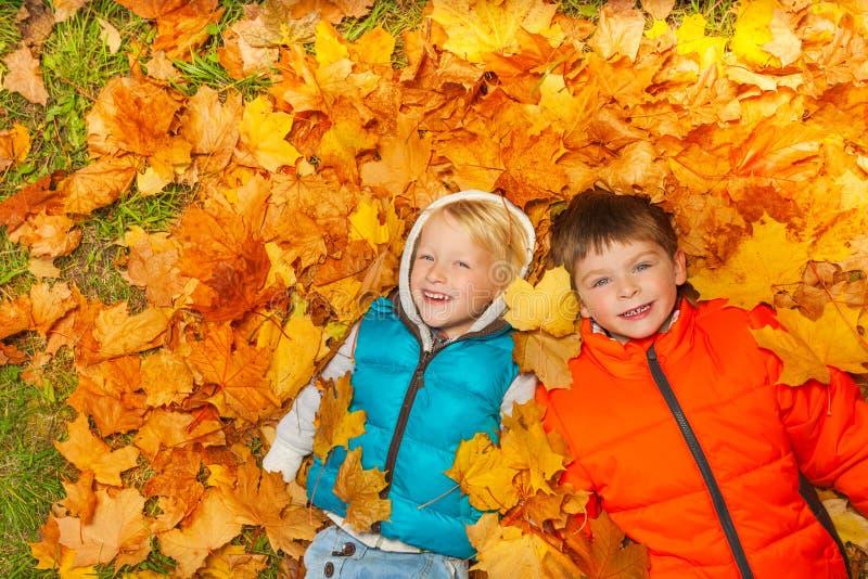 Twee jongens die op de mening van de herfstbladeren vanaf bovenkant leggen stock fotografie