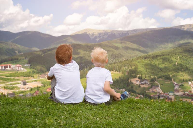 Twee jongens die op een heuvel zitten en de bergen bekijken Rug vi royalty-vrije stock fotografie