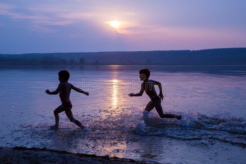 Twee jongens die op het strand van de rivier tegen zonsondergang lopen stock foto