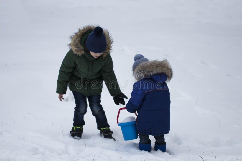 Twee jongens die op sneeuw in de wintertijd spelen royalty-vrije stock afbeelding