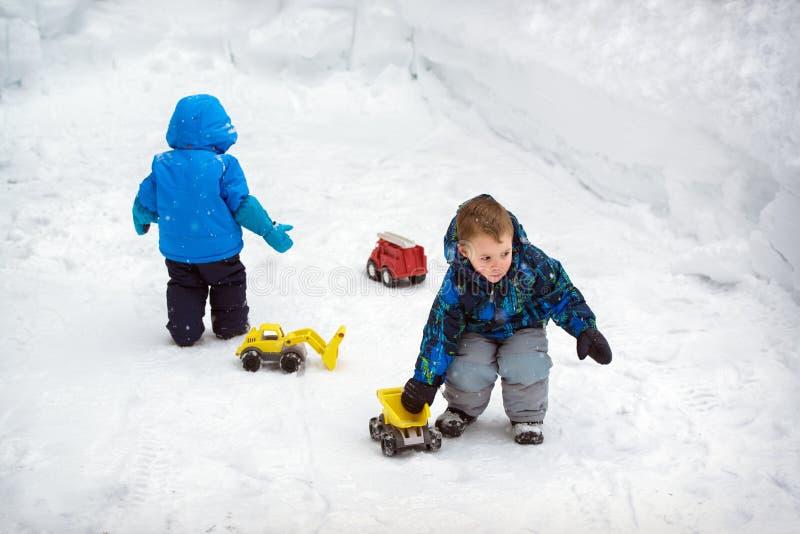 Twee Jongens die in Sneeuw met Vrachtwagens spelen stock foto's