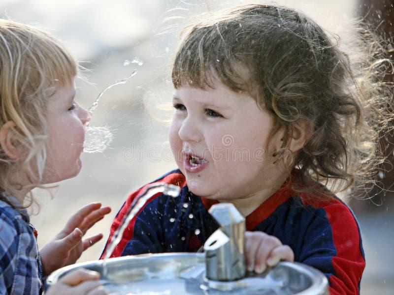 Twee jongens door de het drinken fontein stock foto