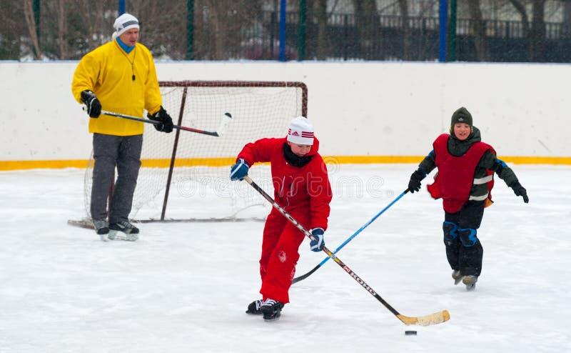 Twee jongens en volwassen mensen speelijshockey 26 11 2019 royalty-vrije stock foto