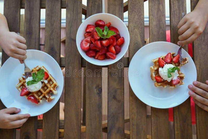 Twee jongens eten voor Ontbijt Weense wafels met roomijs en aardbeien Hoogste mening royalty-vrije stock foto's
