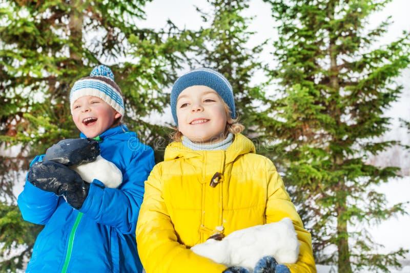 Twee jongens met grote brok van sneeuw in het park royalty-vrije stock afbeelding