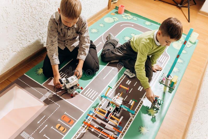 Twee jongens spelen met robots dietot zij van de robotachtige aannemer op de kleurrijke banner op de vloer in leidden royalty-vrije stock afbeelding