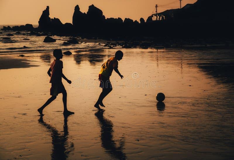 Twee jongens spelen voetbal op strand in schemer, Goa, India royalty-vrije stock afbeeldingen