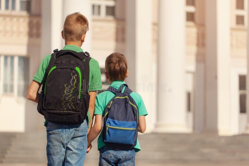 Twee jongens van het schooljonge geitje met rugzak op zonnige dag De gelukkige kinderen gaan naar school Achter mening royalty-vrije stock fotografie