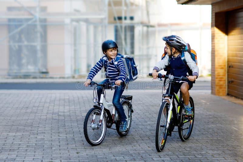 Twee jongens van het schooljonge geitje in veiligheidshelm het berijden met fiets in de stad met rugzakken Gelukkige kinderen in  stock foto's