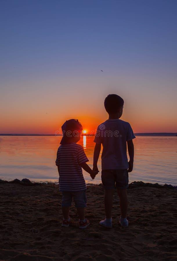 Twee jongensbroers letten op de mooie zonsondergang stock afbeeldingen