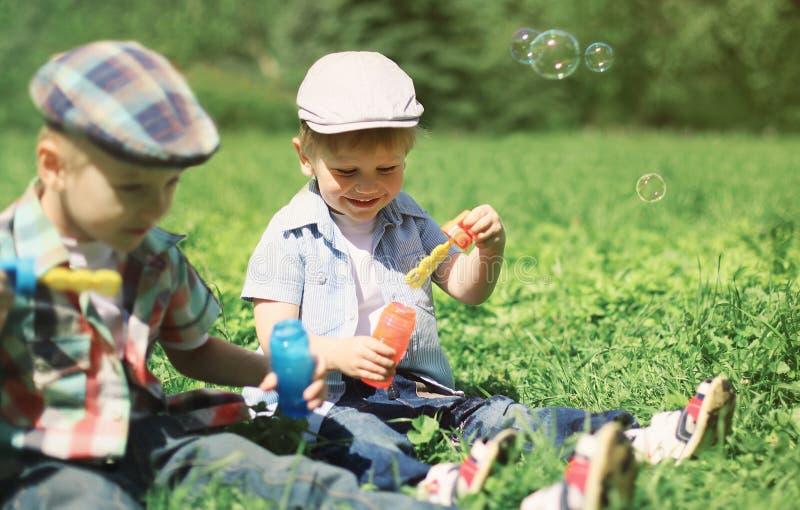 Twee jongenskinderen die op de gras blazende zeepbels zitten stock fotografie