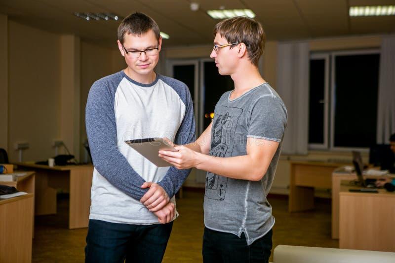 Twee jongeren bespreekt een project in het bureau Zich bevindt naast elkaar, vertelt één van hen andere over zijn projec stock foto