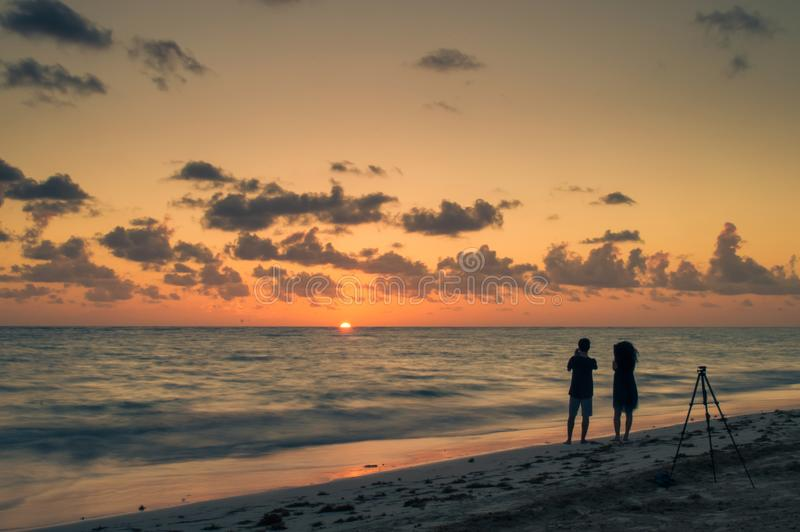 Twee jongeren bij het strand die beelden nemen bij gouden uur royalty-vrije stock foto