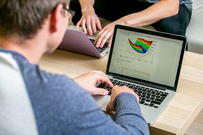 Twee jongeren die aan laptops in het bureau werken, die een programma schrijven, verbetert de tekst Zit bij de lijst tegenover el stock fotografie
