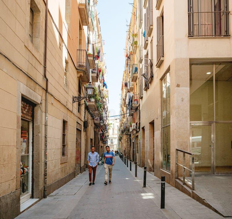 Twee jongeren die de uiterst kleine straat Barcelona lopen royalty-vrije stock afbeeldingen