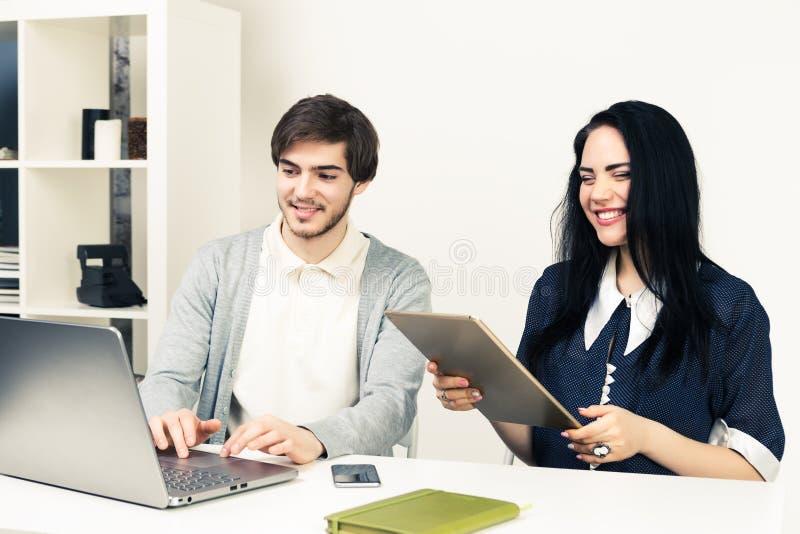 Twee jongeren die samen met laptop en tablet werken terwijl het zitten op minimalistic wit kantoor stock afbeelding