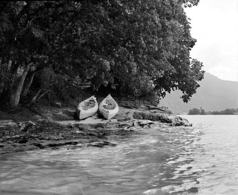 Twee kano's op rotsachtig strand op rand van meer royalty-vrije stock foto's