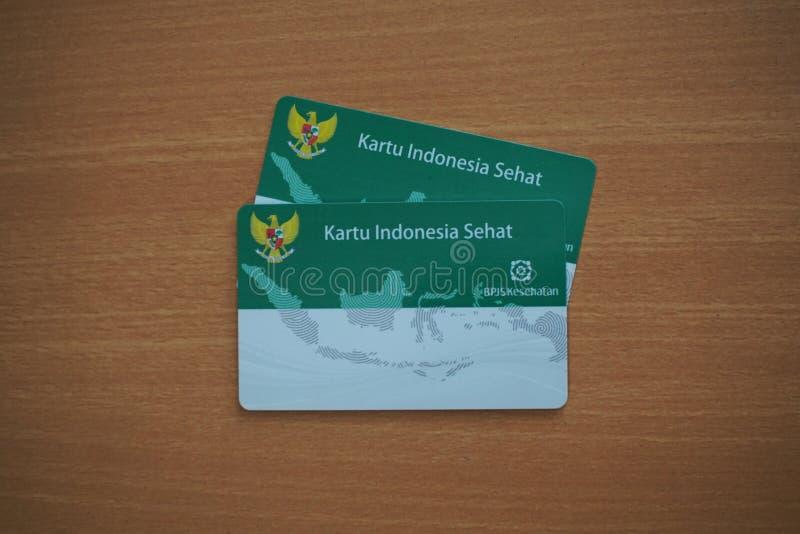 Twee Kartu Indonesië Sehat of KIS (de Overheidsziekteverzekeringskaart van Indonesië) op een houten lijst stock afbeelding