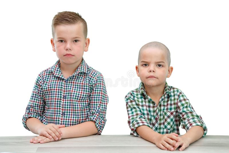 Twee Kaukasische jongens, broers in plaidoverhemden die op een licht geïsoleerde achtergrond stellen Het onderzoeken van de camer royalty-vrije stock foto's