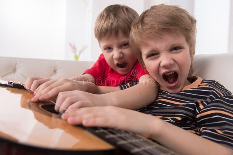Twee Kaukasische jongens die akoestische gitaar spelen royalty-vrije stock fotografie