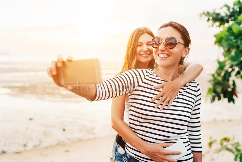 Twee Kaukasische meisjes die en voor selfie aan de overzeese partij koesteren stellen die smartphone gebruiken Achteloos het conc stock foto