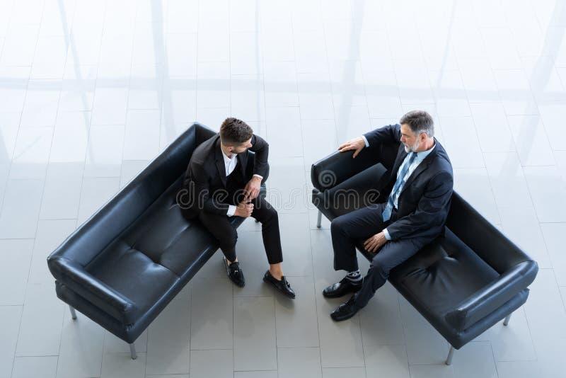 Twee Kaukasische mensen bij een commerciële vergaderingszitting op een bank in het commerciële centrum lobbyen stock foto