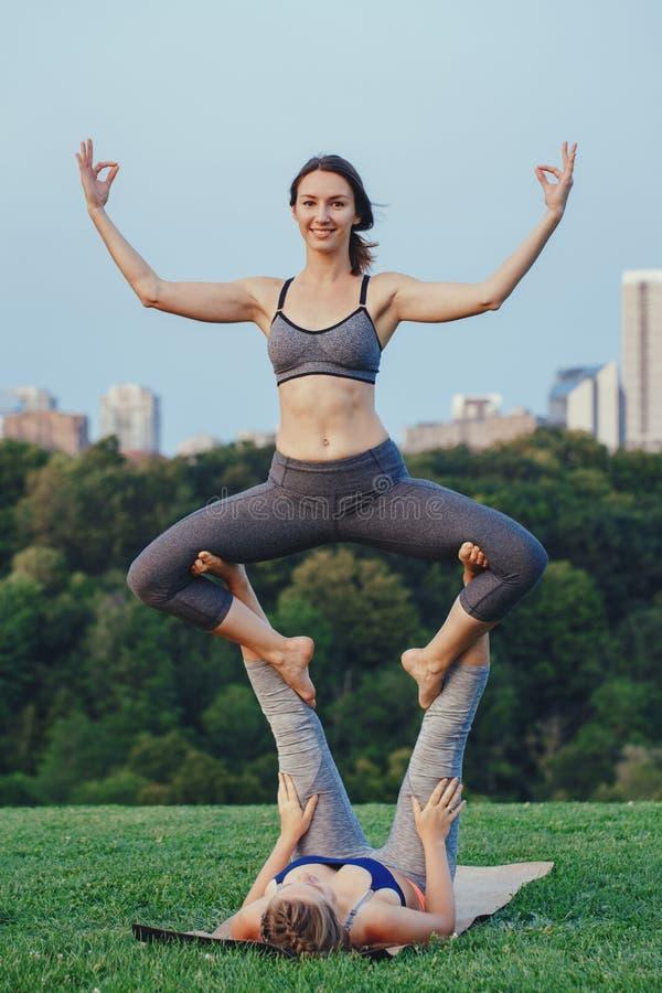 Twee Kaukasische vrouwen die yoga uitrekkende training in park doen in openlucht bij zonsondergang stock fotografie