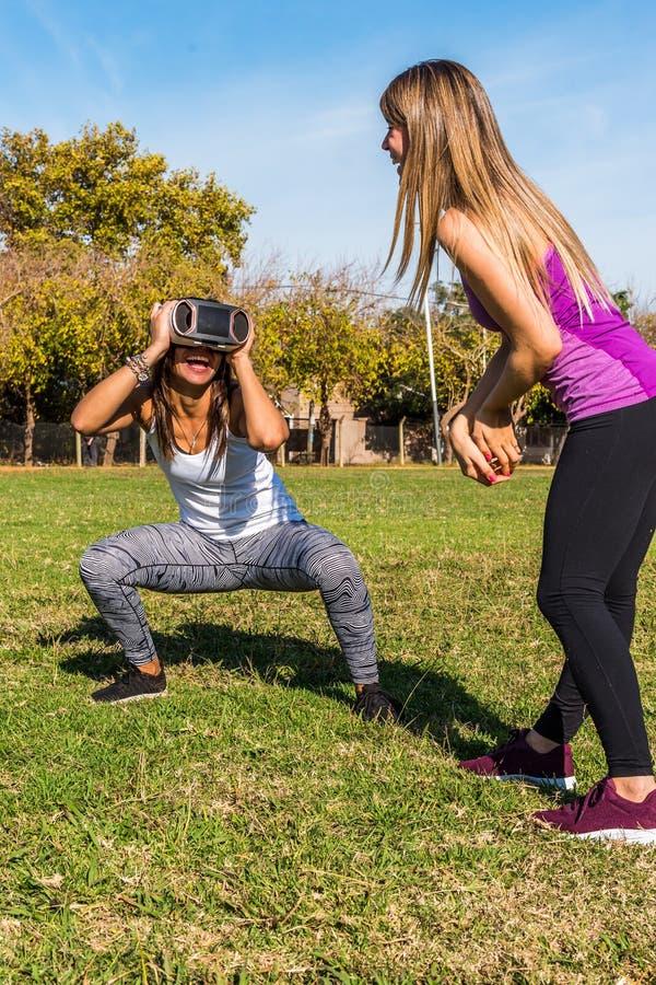 Twee Kaukasische vrouwen in het park, een blonde en een ander brunette met een virtueel werkelijkheidsmasker stock fotografie