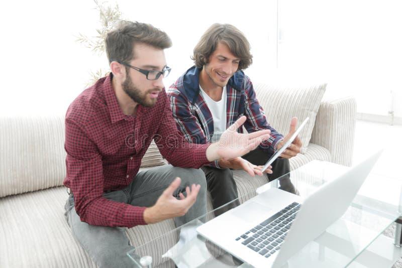 Twee kerels die op de laag zitten en het laptop scherm bekijken stock fotografie