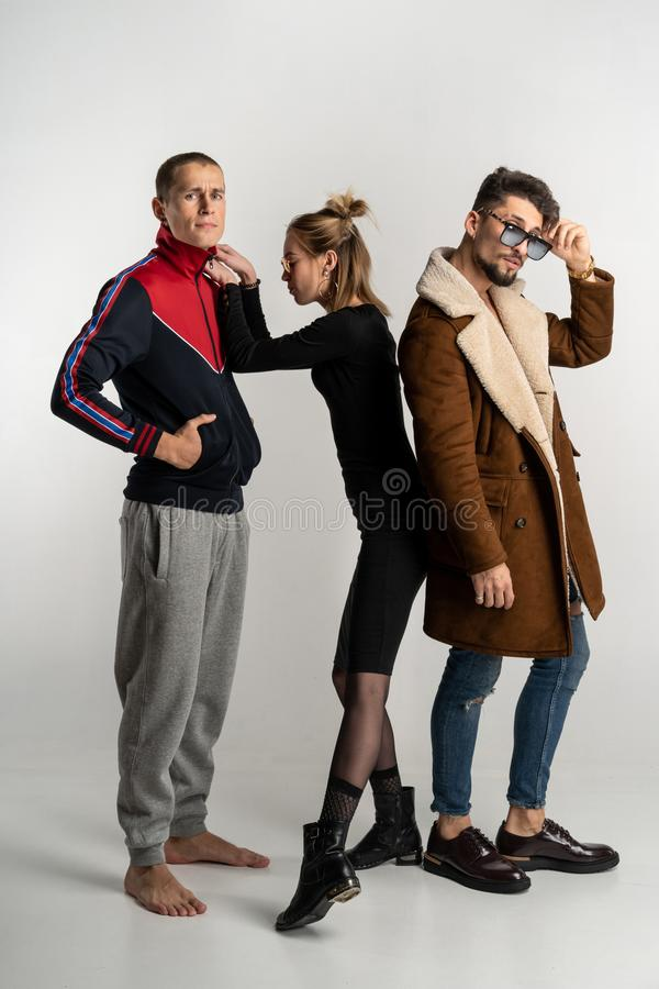 Twee kerels en meisje in modieuze toevallige heldere en donkere kleurrijke kleren stock foto