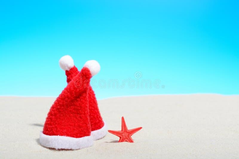 Twee Kerstmanhoeden naast een zeester op een zonnig strand stock fotografie