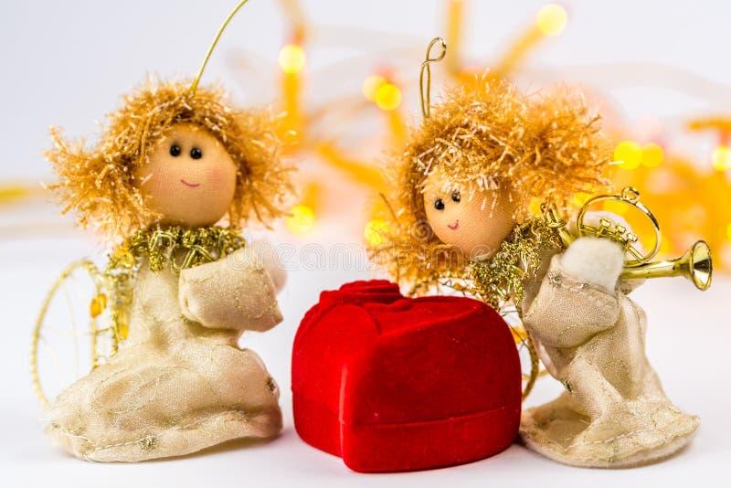 Twee Kerstmisengelen en rood fluweelhart op witte achtergrond stock fotografie