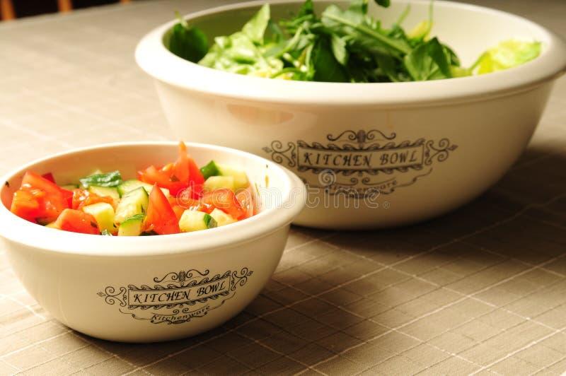 Twee keukenkommen die met verse salade worden gevuld stock fotografie
