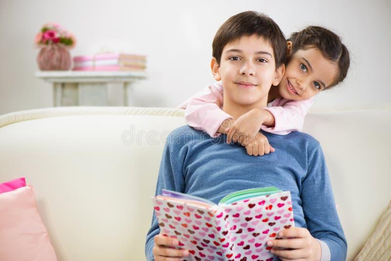 Twee kinderen die boek thuis lezen stock foto's