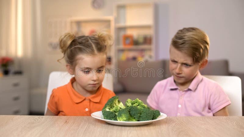 Twee kinderen die broccoli, onsmakelijke maaltijd, smaakloos gezond voedsel bekijken royalty-vrije stock afbeelding