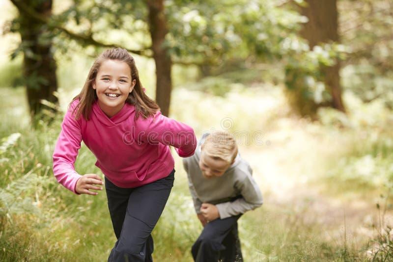 Twee kinderen die in een bos onder groen lopen die bij camera, vooraanzicht, nadruk op voorgrond glimlachen royalty-vrije stock foto's