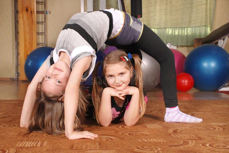 Twee kinderen die in een gymnastiek stellen stock afbeeldingen