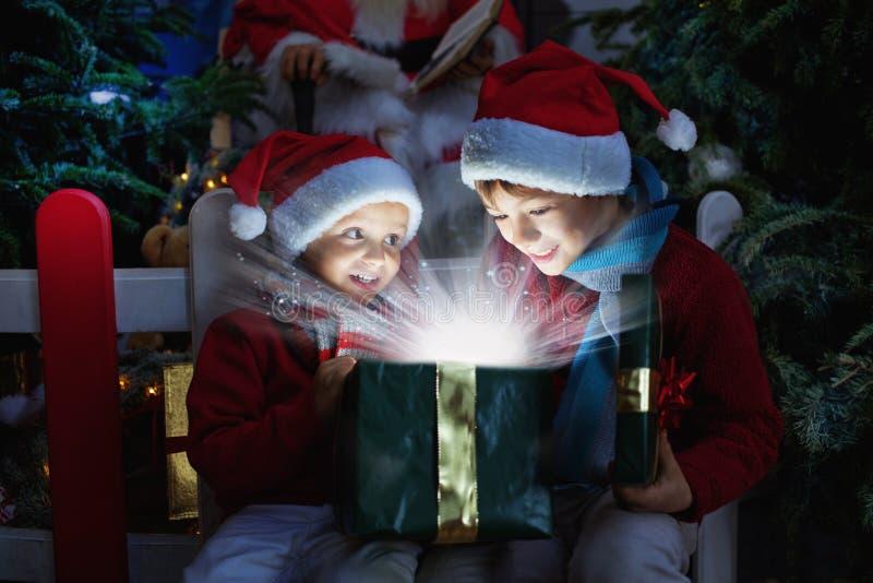 Twee kinderen die Kerstmisgift openen stock afbeeldingen